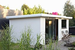 White summer house and terrace in summery garden