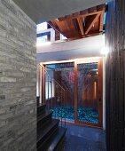 Blick vom Flur mit schwarzer Steintreppe und Galerie auf Innenhof mit kahlem Baum in modernem Architekturambiente