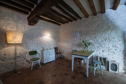 Kitchen table and wooden stools against white-painted stone wall below rustic wood-beamed ceiling