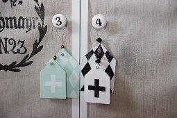 Shabby-chic tags with graphical patterns hanging from furniture knobs