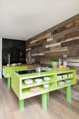Custom kitchen counter painted lime green and wall clad in vintage wooden boards