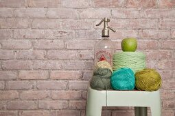 Crochet yarn in shades of green and blue and vintage soda siphon on vintage stool against brick wall