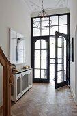 Eleganter Eingangsbereich einer Villa, Flügeltür aus Holz und Glas, moderne Pendelleuchte an Stuckdecke