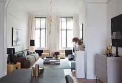 Essplatz vor Rundbogen und Blick in eleganten Wohnbereich mit hohen Fenstern und hellen, bodenlangen Vorhängen