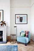 Zimmerecke mit blauem Polstersessel und Metall-Beistelltisch vor Wand mit gerahmter Fotokunst