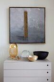 Elegante Schalen auf moderner hellgrauer Kommode an Wand mit Goldrahmen-Gemälde