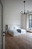 Blick durch offene Tür auf Doppelbett mit hohem, weißem Kopfteil in minimalistischem Schlafzimmer mit Fischgrätparkett