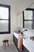 Waschtischzeile mit trogartigen Becken aus Marmor, oberhalb Spiegelschrank an Wand
