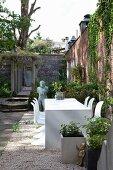 Weißer Tisch und Klassiker Schalenstühle in traditionellem Innenhof vor begrünter Ziegelmauer