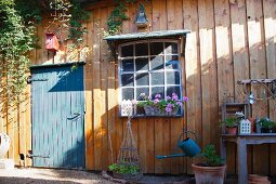 Blue-grey wooden door and flowering geraniums below lattice window in façade of idyllic wooden cabin