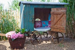 Vintage-style play house on cart and basket of flowering hydrangeas