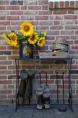 Sunflowers in vintage tin on metal welly stand against brick wall