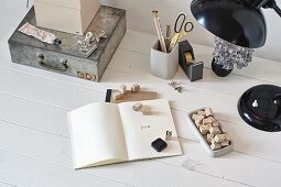A notebook with a letter stamp, a metal tin, a pencil holder and a black table lamp on a white desk