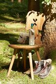 Wooden chair, hiking utensils, wine bottle wrapped in map and walking boots below tree