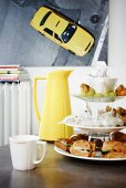 Cake stand, white coffee cup and yellow thermos flask in front of retro picture of car