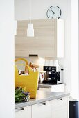 Yellow shopping bag on kitchen counter in front of coffee machine