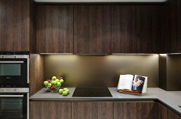 Ceramic hob and fitted appliances in fitted kitchen with dark brown wooden fronts