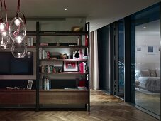 Flatscreen TV on living room shelving, glass bubble pendant lamps n foreground and bedroom reflected in glass wall