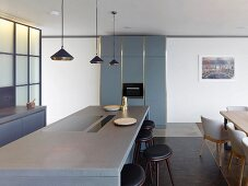 Island counter with hob and bar stools in open-plan kitchen