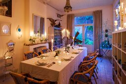 Wicker chairs around set table in candlelit dining room
