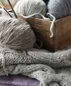 Strickzeug & verschiedene graue Wollknäuel in Holzkiste