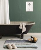 A knitted bath mat in front of a free-standing bath tub