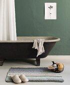 Selbstgestrickter Badteppich vor freistehender Badewanne