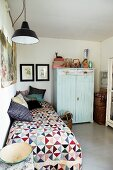 Colourful quilt and various scatter cushions on single bed next to pale blue wardrobe in simple bedroom