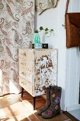 Ladies' bots with floral pattern next to shabby-chic chest of drawers against white wall of hall next to patterned curtain