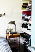 Lamp on antique side table next to open-fronted shelves of clothes on white wooden wall