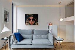 Elegant, grey, designer sofa, black side tables, designer lamps and glass balustrades