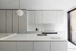 White, designer kitchen with wall units, tall cupboards and island counter