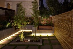 Illuminated, modern, terrace-house garden with wooden screens and view of neighbouring old building