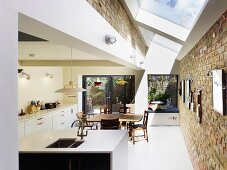 Strip of skylights with white frames and old brick walls in open-plan kitchen with dining area and view of seating area on summery terrace