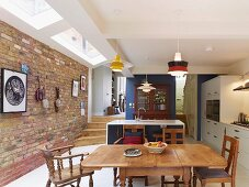 Open-plan kitchen with traditional dining area, antique glass-fronted cupboard against blue partition, strip of modern skylights with white frames and brick wall