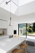 White, modern interior with view of garden