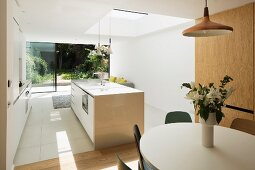 Vase of flowers on dining table in open-plan, white, designer kitchen with skylight and glass wall with view into summery garden