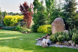 Gardens landscaped with boulders and stepping stones in lawn and view of forest