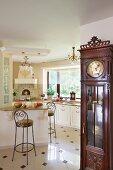 Antike edle Standuhr und offene weiße Landhausküche mit Kronleuchtern