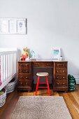 Holzhocker mit rot lackiertem Gestell vor Schreibtisch aus Massivholz neben Gitterbett