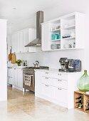 Weisse Einbauküche im Landhausstil mit Edelstahl-Gasherd und Dunstabzugshaube