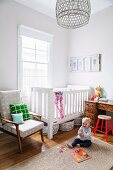 Kleinkind auf Sisalteppich vor weissem Gitterbett und Retrosessel neben Fenster in Zimmerecke