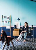 Woman on swivel armchair at desk and decorative ladder in front of blue wall base, decorative floor with circular pattern, in front a Scandinavian upholstered chair