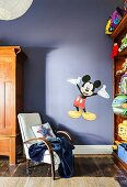 Retro armchair against purple wall with 'Mickey Mouse' wall sticker in children's room