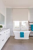 Freestanding country house bathtub in front of window with roller blind next to white vanity unit