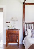 Wooden bedside table with table lamp next to bed with canopy frame