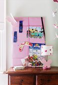 Pink pin board with drawing, calendar and boomerang behind table lamp on wooden chest of drawers