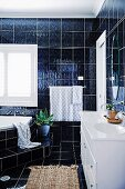 Bathroom with dark wall and floor tiles, corner bath with step and white vanity unit