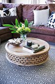 Round floor table made of decorated mango wood on a geometrically patterned carpet in front of a comfortable sofa with cushions