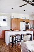 Bar stools in front of a white counter in an open kitchen, fitted wardrobes with a wooden front and retro flair